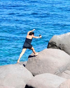 Eine Frau springt über Klippen | lacapocuoca.at